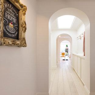 他の地域のトランジショナルスタイルのおしゃれな廊下 (白い壁、塗装フローリング、白い床) の写真