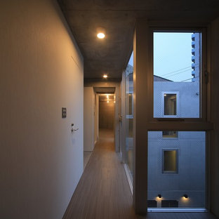 Photo of a mid-sized modern hallway in Tokyo with white walls, linoleum floors and beige floor.
