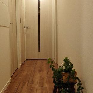 他の地域の小さい北欧スタイルのおしゃれな廊下 (白い壁、合板フローリング、茶色い床) の写真