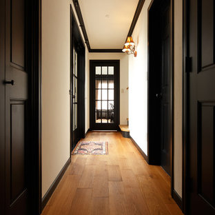 Midcentury hallway in Other with white walls, medium hardwood floors and brown floor.