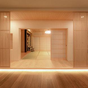Foto på en orientalisk hall, med vita väggar och ljust trägolv