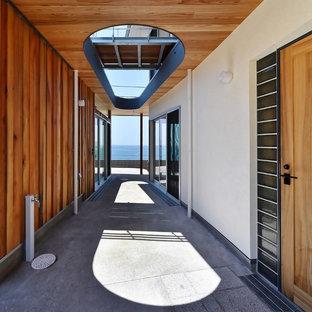 他の地域のコンテンポラリースタイルのおしゃれな廊下 (マルチカラーの壁、コンクリートの床、グレーの床) の写真