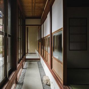 他の地域の巨大な和風のおしゃれな廊下 (白い壁、コンクリートの床、グレーの床) の写真