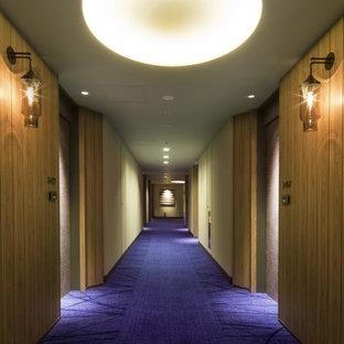 На фото: огромный коридор в скандинавском стиле с коричневыми стенами, ковровым покрытием, фиолетовым полом, потолком с обоями и панелями на стенах