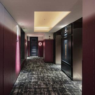 Inredning av en modern mycket stor hall, med röda väggar, heltäckningsmatta och grönt golv