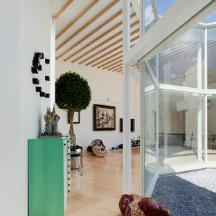 Aménagement d'un couloir moderne avec un mur blanc, un sol en bois peint, un sol beige, un plafond en poutres apparentes et du lambris de bois.