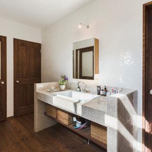 他の地域のアジアンスタイルのおしゃれな浴室 (オープンシェルフ、ベージュのタイル、タイルの洗面台、白い壁、濃色無垢フローリング、オーバーカウンターシンク、茶色い床) の写真
