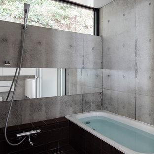 横浜のインダストリアルスタイルのおしゃれな浴室 (コーナー型浴槽、グレーの壁、黒い床) の写真