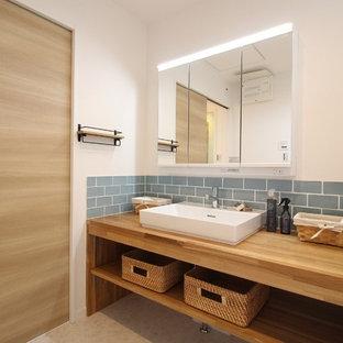 他の地域のアジアンスタイルのおしゃれな浴室 (オープンシェルフ、中間色木目調キャビネット、青いタイル、サブウェイタイル、白い壁、ベッセル式洗面器、木製洗面台、ベージュの床、ブラウンの洗面カウンター) の写真