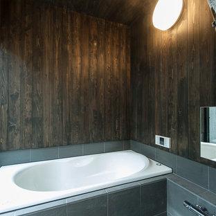 東京23区のアジアンスタイルの浴室・バスルームの画像 (ドロップイン型浴槽、黒いタイル、茶色い壁)