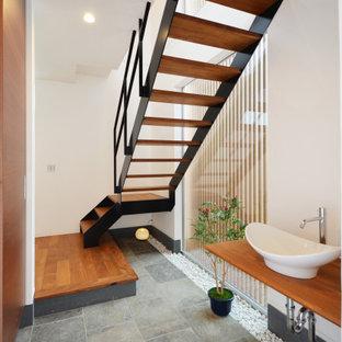 他の地域の広いアジアンスタイルのおしゃれな浴室 (オープンシェルフ、中間色木目調キャビネット、白い壁、ベッセル式洗面器、木製洗面台、グレーの床、ブラウンの洗面カウンター) の写真