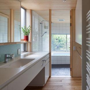 Diseño de cuarto de baño asiático con armarios con paneles lisos, puertas de armario blancas, baldosas y/o azulejos azules, suelo de madera en tonos medios, lavabo integrado y suelo marrón