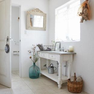 他の地域の中くらいのシャビーシック調のおしゃれなバスルーム (浴槽なし) (家具調キャビネット、白いキャビネット、白い壁、磁器タイルの床、オーバーカウンターシンク、ベージュの床、グレーの洗面カウンター、洗面台1つ、独立型洗面台) の写真