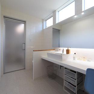 他の地域の中くらいのコンテンポラリースタイルのおしゃれな浴室 (一体型トイレ、白いタイル、磁器タイル、白い壁、ベッセル式洗面器、白い床) の写真