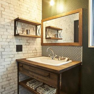 Foto de cuarto de baño industrial con armarios abiertos, puertas de armario de madera oscura, baldosas y/o azulejos en mosaico, paredes negras, lavabo encastrado, encimera de madera, suelo negro y encimeras marrones