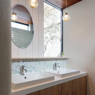他の地域のアジアンスタイルのおしゃれな浴室 (フラットパネル扉のキャビネット、中間色木目調キャビネット、青いタイル、白いタイル、モザイクタイル、白い壁、ベッセル式洗面器、白い洗面カウンター) の写真