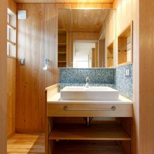 東京都下の中サイズのアジアンスタイルのおしゃれなバスルーム (浴槽なし) (オープンシェルフ、淡色木目調キャビネット、青いタイル、ベージュの壁、無垢フローリング、ベッセル式洗面器、ベージュの床、白い洗面カウンター、ニッチ、洗面台1つ、造り付け洗面台、板張り天井、板張り壁) の写真