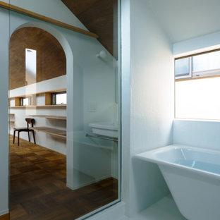 Cette photo montre une petit salle de bain principale moderne avec un placard sans porte, une baignoire indépendante, un espace douche bain, un WC séparé, un carrelage blanc, un mur blanc, un lavabo suspendu, un sol blanc, une cabine de douche à porte coulissante, meuble simple vasque, meuble-lavabo suspendu et un plafond en lambris de bois.