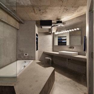 他の地域のインダストリアルスタイルのおしゃれな浴室 (ドロップイン型浴槽、グレーの壁、コンクリートの床、グレーの床) の写真