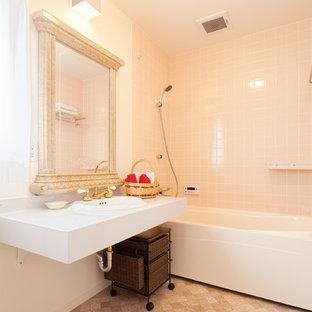 他の地域の中くらいのトラディショナルスタイルのおしゃれなマスターバスルーム (家具調キャビネット、茶色いキャビネット、アルコーブ型浴槽、アルコーブ型シャワー、一体型トイレ、ピンクのタイル、セラミックタイル、白い壁、モザイクタイル、オーバーカウンターシンク、人工大理石カウンター、ベージュの床、シャワーカーテン、白い洗面カウンター) の写真