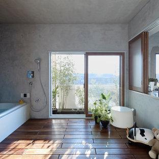 Foto de cuarto de baño minimalista con bañera esquinera, ducha abierta, paredes grises, suelo de madera pintada, suelo marrón y ducha abierta