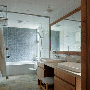 他の地域のコンテンポラリースタイルのおしゃれな浴室 (フラットパネル扉のキャビネット、中間色木目調キャビネット、オーバーカウンターシンク、マルチカラーの床) の写真