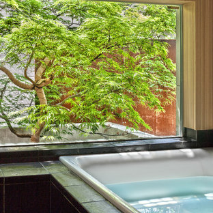 東京23区のアジアンスタイルのおしゃれな浴室 (ドロップイン型浴槽、黒いタイル、茶色い壁) の写真