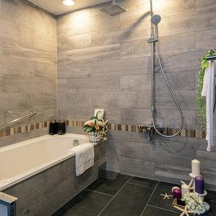 東京23区の中くらいのコンテンポラリースタイルのおしゃれなマスターバスルーム (ドロップイン型浴槽、ダブルシャワー、グレーの壁、黒い床、グレーのタイル、磁器タイル、磁器タイルの床) の写真