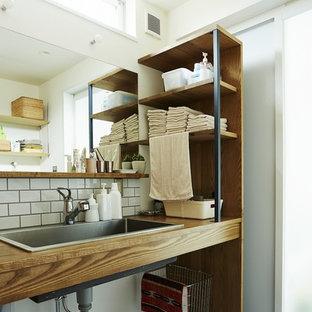 他の地域のビーチスタイルのおしゃれな浴室 (オープンシェルフ、白いタイル、白い壁、オーバーカウンターシンク、木製洗面台、グレーの床、ブラウンの洗面カウンター) の写真