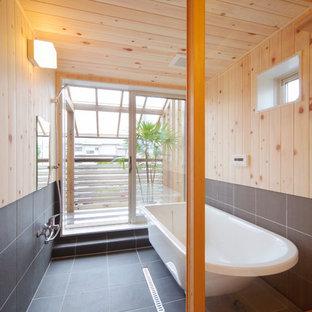 他の地域のアジアンスタイルのおしゃれな浴室 (置き型浴槽、オープン型シャワー、茶色い壁、グレーの床、オープンシャワー) の写真