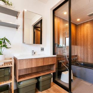 Ejemplo de cuarto de baño actual con armarios abiertos, bañera esquinera, ducha abierta, paredes marrones, suelo de madera clara, suelo marrón y ducha abierta