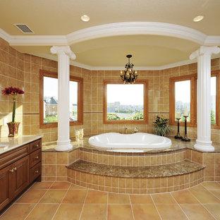 他の地域のトラディショナルスタイルのおしゃれな浴室 (大型浴槽、茶色いタイル、茶色い壁、テラコッタタイルの床、茶色い床) の写真