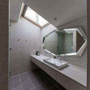 東京都下のコンテンポラリースタイルのおしゃれな浴室 (フラットパネル扉のキャビネット、白いキャビネット、グレーのタイル、ベッセル式洗面器、グレーの床、グレーの洗面カウンター、洗面台1つ、フローティング洗面台、三角天井) の写真