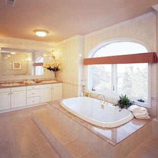 他の地域のヴィクトリアン調のおしゃれな浴室 (レイズドパネル扉のキャビネット、白いキャビネット、コーナー型浴槽、ベージュの壁、大理石の床、ベージュの床) の写真