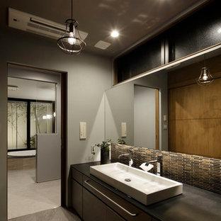 他の地域のアジアンスタイルのおしゃれな浴室 (フラットパネル扉のキャビネット、濃色木目調キャビネット、グレーの壁、ベッセル式洗面器、グレーの床) の写真