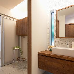 他の地域のコンテンポラリースタイルのおしゃれな浴室 (中間色木目調キャビネット、白いタイル、白い壁、ベッセル式洗面器、木製洗面台) の写真