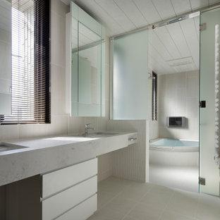 Immagine di una stanza da bagno minimal con ante lisce, ante bianche, vasca ad angolo, zona vasca/doccia separata, lavabo sottopiano, pavimento grigio, porta doccia a battente e top grigio