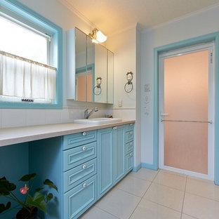 他の地域のトラディショナルスタイルのおしゃれな浴室 (落し込みパネル扉のキャビネット、青いキャビネット、白い壁、茶色い床) の写真