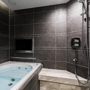 東京23区のモダンスタイルのおしゃれなマスターバスルーム (ドロップイン型浴槽、洗い場付きシャワー、黒いタイル、黒い壁、グレーの床、オープンシャワー) の写真
