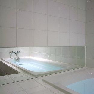 Immagine di una stanza da bagno padronale minimalista con vasca da incasso, piastrelle bianche, piastrelle in ceramica, pareti bianche e pavimento in sughero