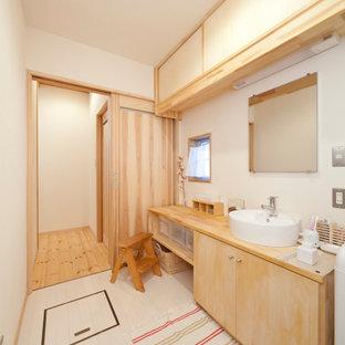 他の地域のアジアンスタイルのおしゃれな浴室 (白い壁、白い床、フラットパネル扉のキャビネット、淡色木目調キャビネット、ベッセル式洗面器、木製洗面台、ベージュのカウンター) の写真