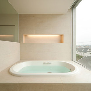 This is an example of a large asian bathroom in Tokyo with beige walls, a hot tub and beige floor.
