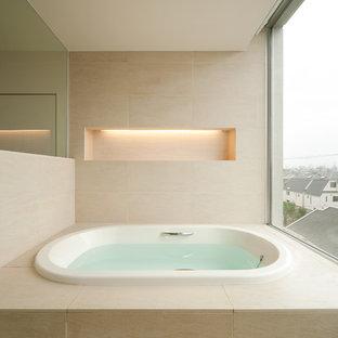 Idée de décoration pour une grande salle de bain asiatique avec un mur beige, un bain bouillonnant et un sol beige.