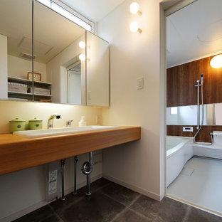 他の地域のインダストリアルスタイルのおしゃれな浴室 (白い壁、クッションフロア、木製洗面台、オーバーカウンターシンク、グレーの床、ブラウンの洗面カウンター) の写真