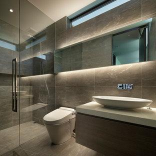 他の地域のコンテンポラリースタイルのおしゃれな浴室 (フラットパネル扉のキャビネット、グレーのキャビネット、グレーのタイル、グレーの壁、ベッセル式洗面器、グレーの床) の写真