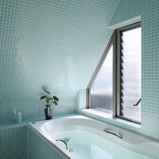 Ispirazione per una stanza da bagno minimal con pareti blu, pavimento blu e vasca ad angolo