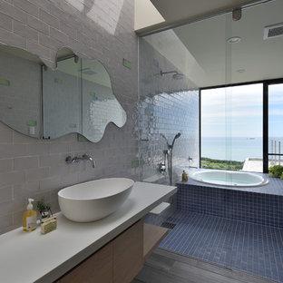 他の地域のコンテンポラリースタイルのおしゃれな浴室 (フラットパネル扉のキャビネット、淡色木目調キャビネット、白いタイル、白い壁、無垢フローリング、ベッセル式洗面器、茶色い床) の写真
