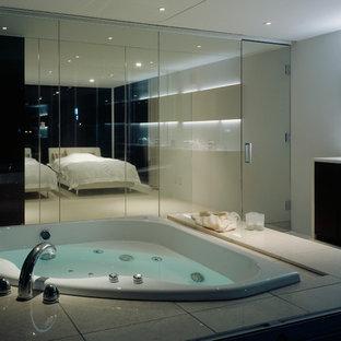 他の地域の広いコンテンポラリースタイルのおしゃれなマスターバスルーム (インセット扉のキャビネット、茶色いキャビネット、コーナー型浴槽、洗い場付きシャワー、一体型トイレ、白いタイル、セメントタイル、白い壁、トラバーチンの床、アンダーカウンター洗面器、人工大理石カウンター、ベージュの床、オープンシャワー、白い洗面カウンター) の写真