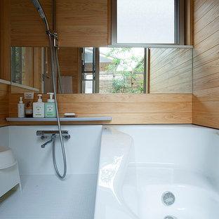 Cette photo montre une salle de bain principale nature de taille moyenne avec un placard à porte affleurante, des portes de placard blanches, une baignoire posée, un espace douche bain, un carrelage beige, un mur beige, un plan de toilette en surface solide, un sol blanc, une cabine de douche à porte battante et un plan de toilette blanc.