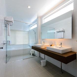 他の地域のコンテンポラリースタイルのおしゃれな浴室 (白いタイル、磁器タイル、白い壁、磁器タイルの床、グレーの床、開き戸のシャワー、ブラウンの洗面カウンター) の写真